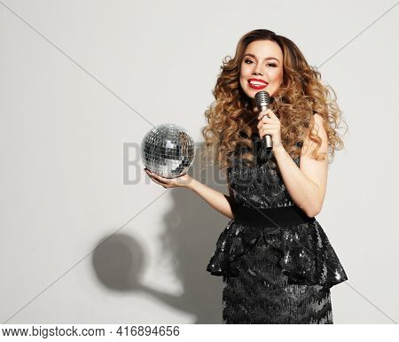 Young blond woman with long curly hair dressed in evening dress holding a microphone and disco ball, singing and smiling