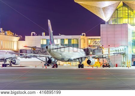 Night Airport Apron, Modern Passenger Airliner At The Jet Bridge