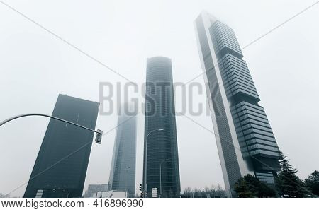 Modern Skyscrapers Architecture View During Foggy Weather. Four Towers Business Area Against Misty S