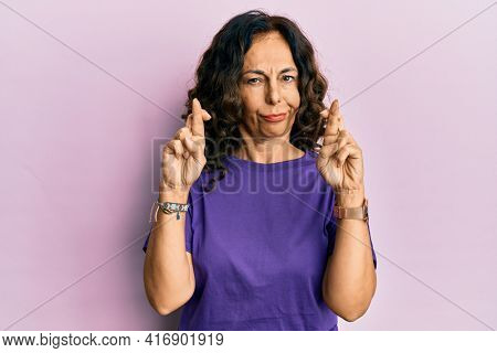 Middle age hispanic woman doing fingers crossed gesture skeptic and nervous, frowning upset because of problem. negative person.