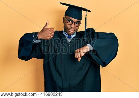Young african american man wearing graduation cap and ceremony robe doing thumbs up and down, disagreement and agreement expression. crazy conflict