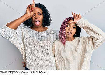 Beautiful african american mother and daughter wearing casual clothes and hugging making fun of people with fingers on forehead doing loser gesture mocking and insulting.