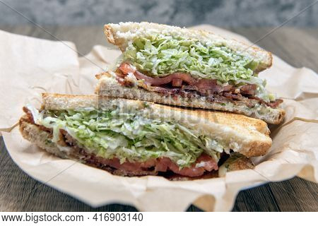 Bacon, Lettuce, Tomato Sandwich Loaded With Meat And Fillings Squeezed Between Two Toasted Slices Of