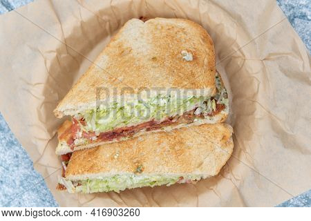 Overhead View Of Bacon, Lettuce, Tomato Sandwich Loaded With Meat And Fillings Squeezed Between Two