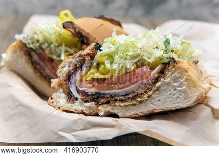 Vegan Sandwich Is Loaded Between Baked Bread With Fried Eggplant, Provolone Cheese, Mayo, And Vinaig