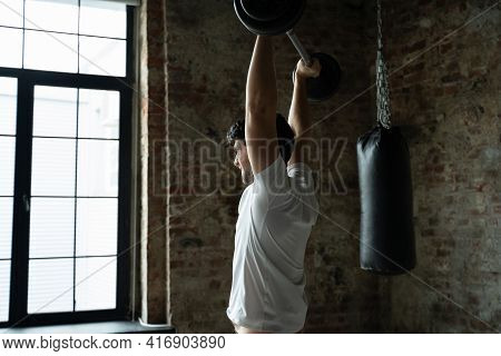 Muscular Fitness Man Lifting Barbell Above His Head In Modern Gym. Functional Training