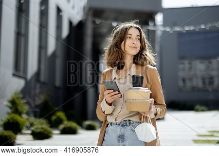 Woman With Protective Mask On Hand Walking With Takeaway Food Near Office Building Alone In The Empt