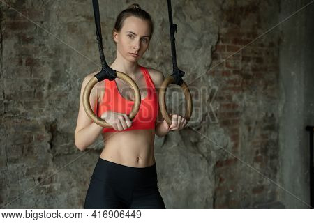 Athlete Woman Holding Gymnastic Rings At The Gym And Looking At Camera. Fitness Woman Looking Tired