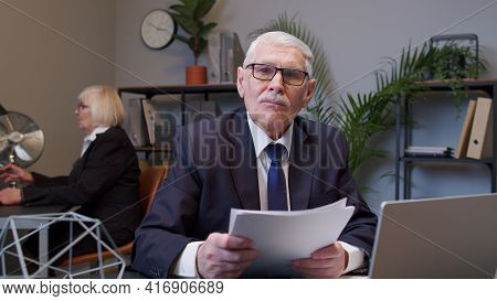 Cheerful Senior Business Company Manager Sitting At Office Desk Reading Resume, Successful Job Inter