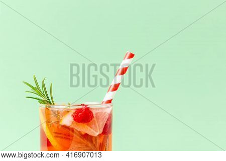 Exotic Red Cold Drink With Lemon, Rosemary And Raspberry With Bicolor Paper Straw On A Mint-color Ba