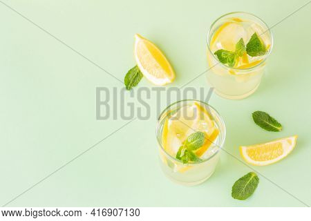 Two Glasses Of Refreshing Summer Drink With Lemon And Mint Leaves On A Green Background. Antioxidant