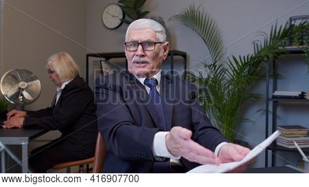 Irritated Elderly Man Boss Raising Hands In Questioning Gesture Why What In Office Room. Elderly Ent