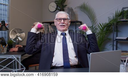 Elderly Smiling Business Man Making Fitness Exercises With Dumbbells After Hard Work While Sits At O