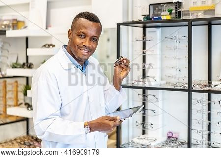 Eyesight And Vision Concept. View Of Smiling African American Attractive Optician Working With Table