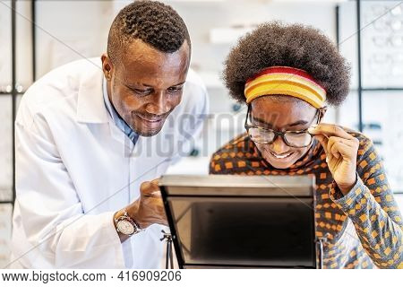 African American Man Professional Optician Helping  And Selling Young Woman African American Choosin