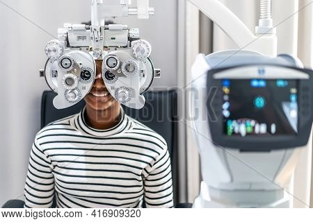 Smiling Young Woman African American Afro Hair Doing Eye Test On Optical Phoropter, Checking On Her
