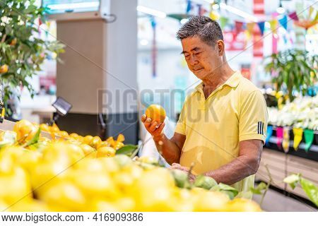 Old Senior Asian Man Looking At Tangerine While Enjoying Grocery Shopping At In The Supermarket