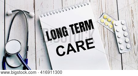 On A Light Wooden Table Lie A Stethoscope, Pills And A Notebook With The Inscription Long Term Care.