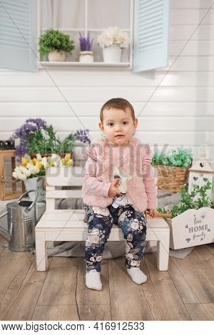 Cheerful Little Girl Child One Year Old Sits On Bench On Veranda. Spring Summer Time. Nature Pastime