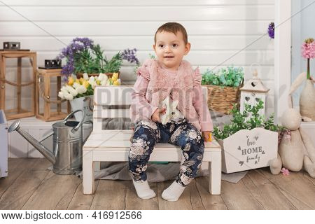 Happy Little Girl Child One Year Old Sits On Bench In Backyard. Smiles Looking Away. Free Time Activ