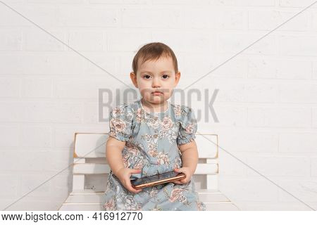 Sad Little Girl Sits On Wooden Bench In Dress And Holds Smartphone In Her Hands.concept Of Replacing