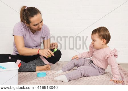 Mother Plays With Her Child At The Doctor, Preparing The Child For The Doctor's Visit.