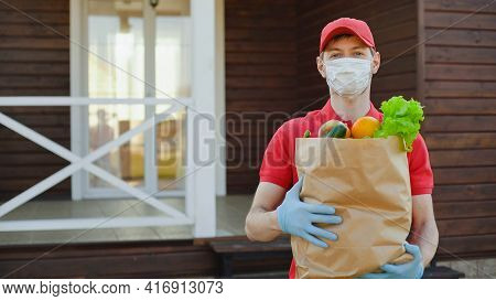 Portrait Of Deliverer In Red Uniform Wearing Safety Mask Holding A Box Of Grocery Food. Delivery Ser