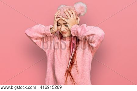 Young caucasian woman wearing casual clothes and wool cap suffering from headache desperate and stressed because pain and migraine. hands on head.