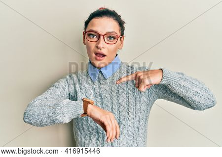 Young caucasian woman wearing casual clothes and glasses in hurry pointing to watch time, impatience, upset and angry for deadline delay