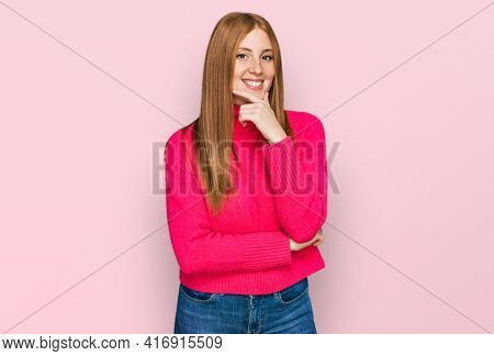 Young irish woman wearing casual clothes looking confident at the camera smiling with crossed arms and hand raised on chin. thinking positive.
