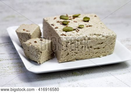 Halva Close-up On A White Plate On A White Wooden Background. Traditional Oriental Dessert Sweet Hal