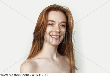 Ginger Woman With Freckles Is Massaging Her Face With A Cream Smiling With Bare Shoulders