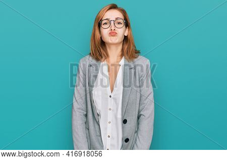 Young caucasian woman wearing business style and glasses puffing cheeks with funny face. mouth inflated with air, crazy expression.
