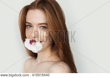 Ginger Woman With Freckles Is Smiling At Camera Holding A Flower In Her Mouth And Wearing Eye Patche