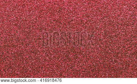 shimmering red color background with glitters on glittery Christmas style material