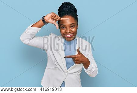 Young african american woman wearing business clothes smiling making frame with hands and fingers with happy face. creativity and photography concept.