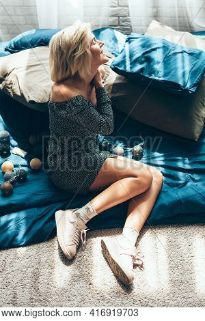 Caucasian Blonde Woman Is Lying On The Floor On A Blanket Near New Year Decorations Smiling In A Sun