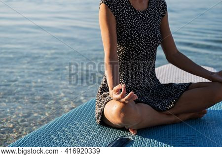 Closeup View Of A Woman Meditating In Lotus Position With Focus On Her Index And Thumb Finger Joined