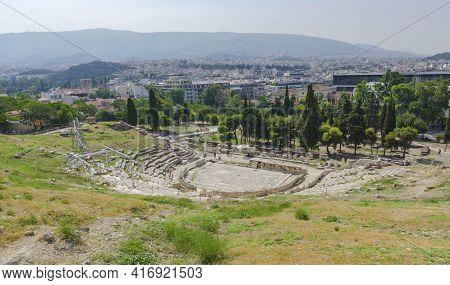 Ancient Dionysus Theater Under The Ruins Of Acropolis, With View Over The City Of Athens, Greece, In