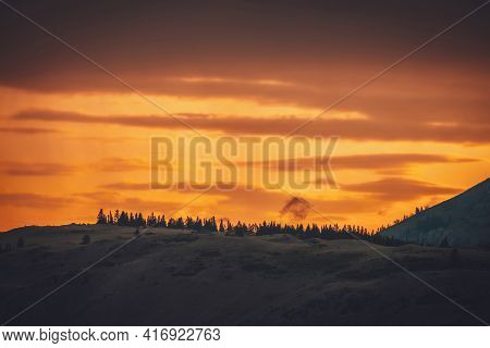 Atmospheric Landscape With Forest Silhouette On Silhouette Of Mountain On Background Of Vivid Orange