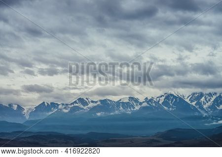 Scenic Mountain Landscape With Great Snowy Mountain Range Among Low Clouds And Green Forest In Valle