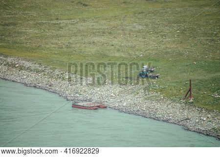Scenic Landscape With Ferry Boat Near Stony Shore Of Wide Mountain River With Turquoise Water. Beaut