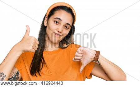 Young hispanic woman wearing casual clothes doing thumbs up and down, disagreement and agreement expression. crazy conflict