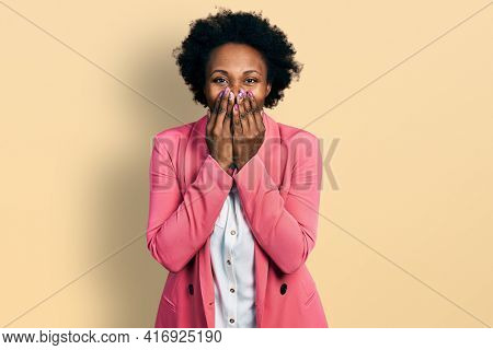African american woman with afro hair wearing business jacket laughing and embarrassed giggle covering mouth with hands, gossip and scandal concept