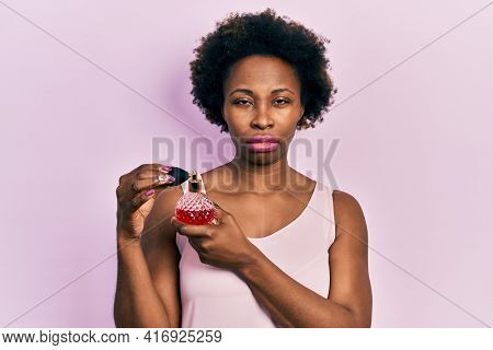 Young african american woman holding perfume skeptic and nervous, frowning upset because of problem. negative person.