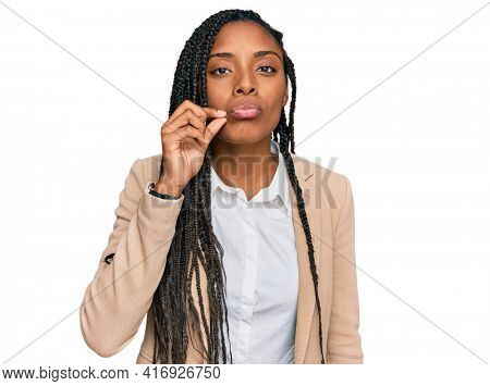 African american woman wearing business jacket mouth and lips shut as zip with fingers. secret and silent, taboo talking