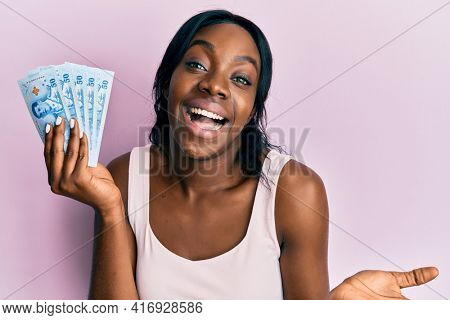 Young african american woman holding thai baht banknotes celebrating achievement with happy smile and winner expression with raised hand