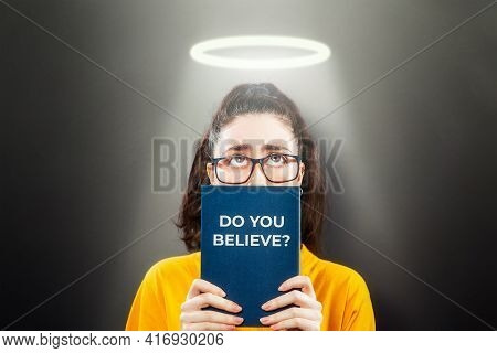 Religion.portrait Of A Woman On A Dark Background, Looking Up From Behind A Book.inscription On The