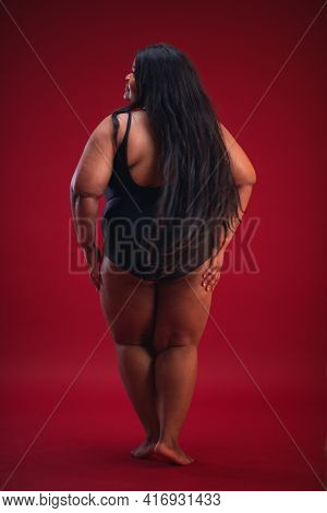 Young Plus Size Woman In Swimsuit On The Red Background