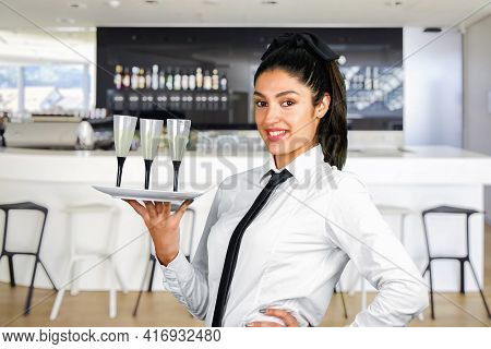 A Girl Waiter With Three Glasses Of Champagne On A White Plate Poses In Front Of A Restaurant Counte